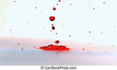 Red ink bouncing on vibrating surface in slow motion