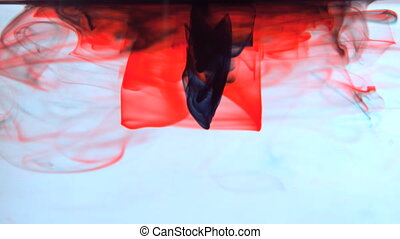 Red and black ink swirling in water in slow motion