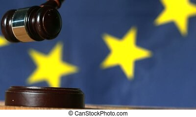 Gavel falling onto sounding block with european union flag...