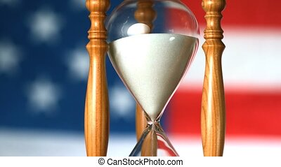 Sand flowing through hourglass with