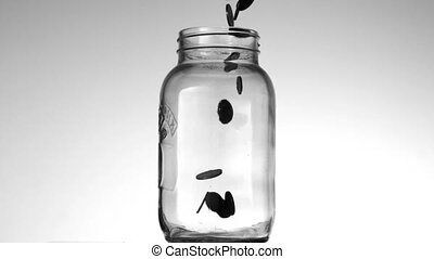 Many coins pouring into glass jar on white background in...