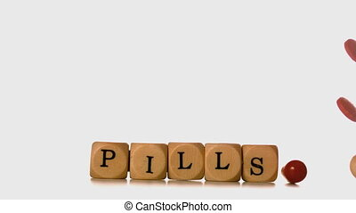 Many types of pills pouring over dice spelling pills in slow...
