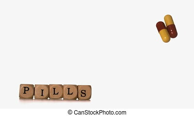Two capsule tablets falling beside dice spelling pills in...