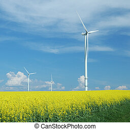 farm of windturbines close to rape field France