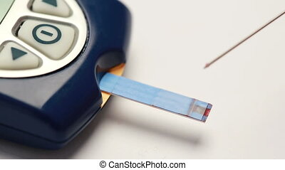 Drop of blood syringed onto test strip of glucose monitor...