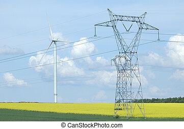 A electric pylon near windturbine over rape field France