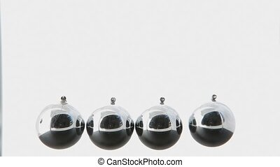 Close up of newtons cradle in motion on white background