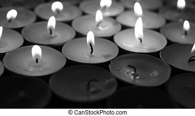 Hand lighting candles with birthday candle in black and...