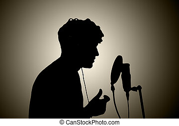 man in headphones singing into a microphone on a white background