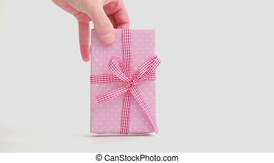 Hand putting down pink gift wrapped present with gingham...
