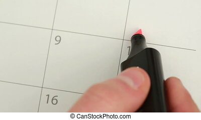 Man circling mothers day on calendar with pink highlighter...