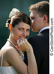 Close up of smiling bride on wedding day leaning on shoulder...