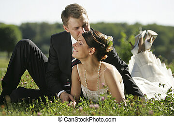 Newlywed couple kissing in field in countryside