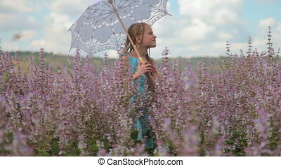 Little girl with a lace parasol on blossoming meadow in...
