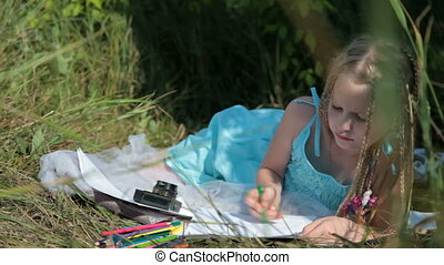 Child drawing with colored pencils on the nature