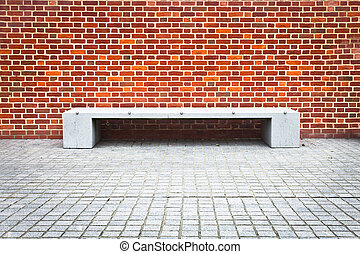 Stone bench - A modern stone bench against a brick wall with...