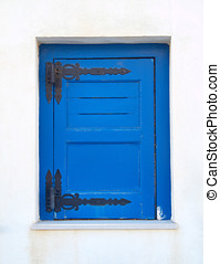 blue painted window shutters on white wall
