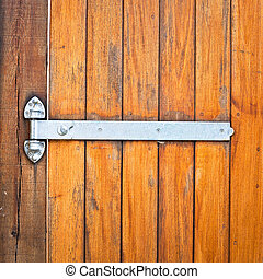 Hinge - A modern metal hinge on a wooden door