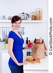 Happy woman unpacking groceries in the kitchen