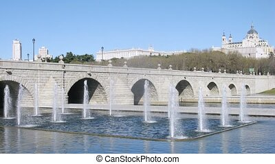 Bridge Puente de Segovia stands against Cathedral and sky -...