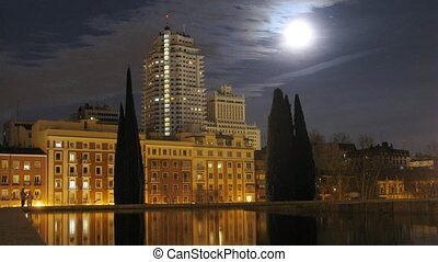 High-rise building stands against night sky and floating...