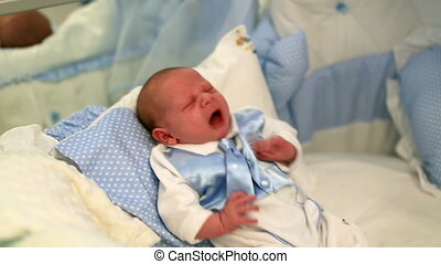 newborn baby crying on the bed