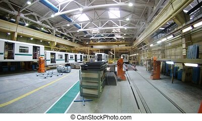 New white carriages of train stand in assembly shop of plant...