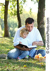 father with a young daughter read the Bible in nature -...