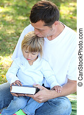 father with a young daughter read the Bible in nature