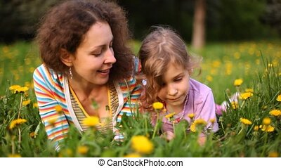 Mother and daughter lie on green glade with yellow dandelions