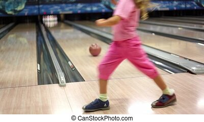 Little girl in pink clothes throws bowling ball and walks away