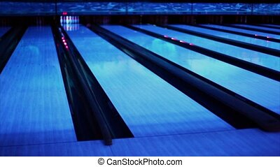 Ball thrundles in flume near bowling lane at dark club