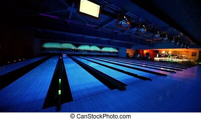 Ball rolls and beats skittles on bowling lane with illumination
