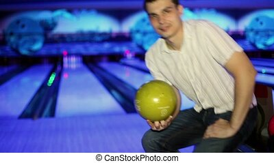 Young man throws bowling ball to beat skittles in dark club