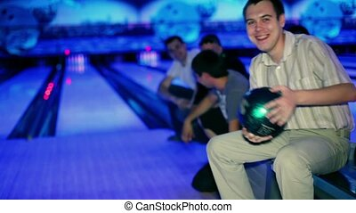 man hold bowling ball, then throws it, friends encourage him