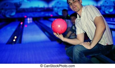 man holds bowling ball and then throws it, friends support him