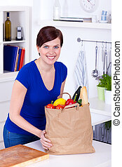 Woman with shopping bag in the kitchen
