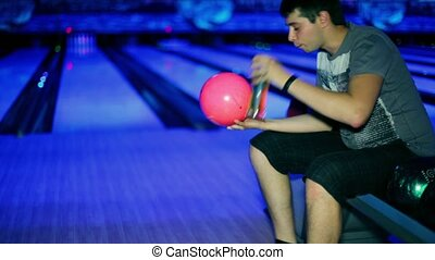 Young man drink beer and make split by beats two skittles on each sides in bowling game