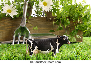 Spring herbs and flowers in the grass with toy cow - Fresh...