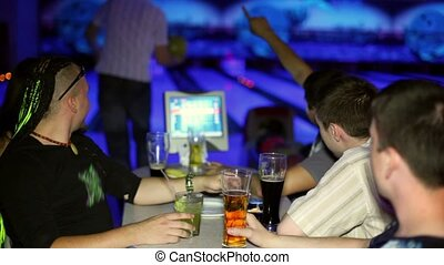 Young man plays bowling and his friends drink beer in dark...
