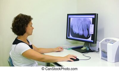 Doctor sits at work table and watches x-ray picture on...