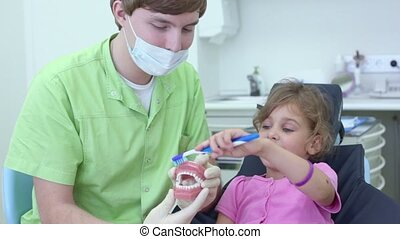 Dentist holds jaw and girl cleans teeth by brush