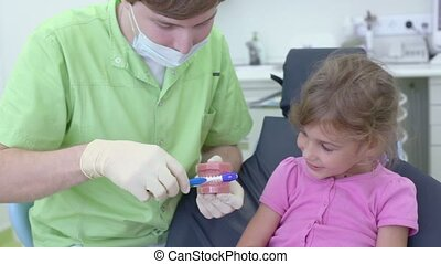 Dentist shows for little girl how to clean teeth by brush