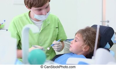Dentist holds dental tool and girl talk about her problems -...