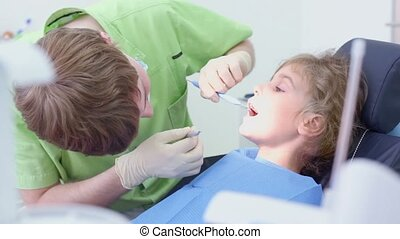 Dentist examines girls teeth with dental tool mirror and hook