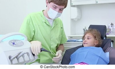 Dentist takes spit suction tool and blows wind on girls arm...