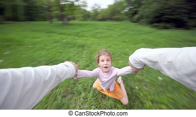 Hand holds little girl which flies above grass at background...