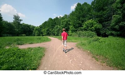 Little boy walks by earthen road near forest, view from behind