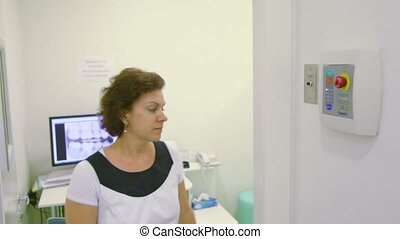 Nurse comes out of room and pushes button for x-ray...