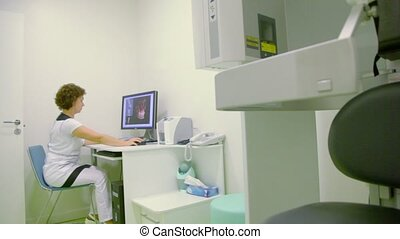 Doctor sits at work table and watches on display of computer